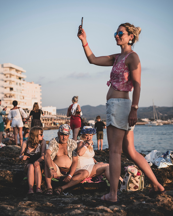 As sunset approaches, a woman takes a selfie as other tourists sit on the rocks near Cafe Mambo in Sant Antoni, Ibiza. (August 2018)