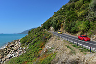 Two cars drive beside the sea on the Captain Cook Highway, also called State Route 44, which connects Cairns and Mossman in Queensland, Australia.