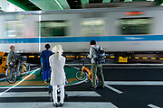 People wait at a level crossing while an Otaku Line train passes by. Shibuya, Tokyo, Japan. Friday April 28th 2017