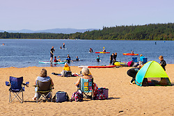 Aviemore, Scotland, UK. 26th August 2021.  Sunshine and high temperatures of over 22C brought water sports enthusiasts and sun worshippers to the popular Watersport centre and beach at Loch Morlich in Glenmore Forest Park in the Cairngorms near Aviemore in the Scottish Highlands today.  Iain Masterton/Alamy Live News.