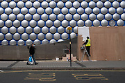 Workman painting a boarded up entrance to the iconic Selfridges shopping centre as a passer by in a face mask walks by in Birmingham city centre is virtually deserted due to the Coronavirus outbreak on 31st March 2020 in Birmingham, England, United Kingdom. Following government advice most people are staying at home leaving the streets quiet, empty and eerie. Coronavirus or Covid-19 is a new respiratory illness that has not previously been seen in humans. While much or Europe has been placed into lockdown, the UK government has announced more stringent rules as part of their long term strategy, and in particular social distancing.