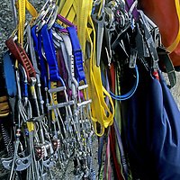 ROCK CLIMBING. Climbing hardware stored at a big-wall belay station, including (L to R) chocks, camming devices (cams), slings & pitons. Great Sail Peak expedition, Baffin Island, Nunavut, Canada.