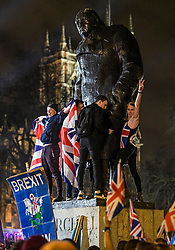 © Licensed to London News Pictures. 31/01/2020. London, UK.  Supporters of Brexit climb on to a statue of former British Prime Minster Winston Churchill in Parliament Square, at 11pm, as the UK leaves the European Union. 51. 9% of the UK population voted to leave the EU in a referendum in June 2016. Photo credit: Ben Cawthra/LNP