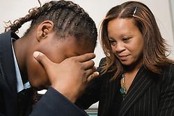 Teacher comforting one an upset secondary school pupil,