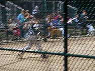 A long exposure motion blurs a home run swing baseball batter seen through the diamond-shaped grid of the backstop.