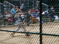A long exposure motion blurs a home run swing baseball batter seen through the diamond-shaped grid of the backstop.