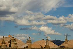 Stone roofs under puffy clouds, Cuzco, Peru, South America
