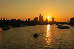 © Licensed to London News Pictures. 01/09/2018. London, UK.  A boat travels on the River Thames at sunrise, seen behind City of London skyscrapers on the first day of meteorological autumn.  Photo credit: Vickie Flores/LNP