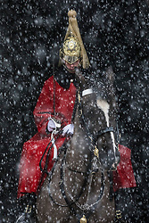 © Licensed to London News Pictures. 27/02/2018. London, UK. A member of the Household Cavalry Mounted Regiment stands on guard as heavy snow falls on Whitehall. Severe cold, blizzards and heavy snow are expected for the rest of the week as the 'Beast from the East' brings freezing Siberian air to the UK. Photo credit: Rob Pinney/LNP