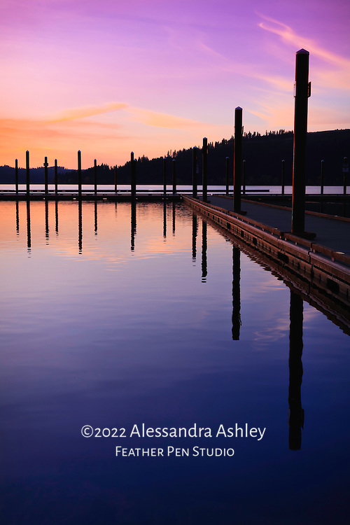 Interplay of cool and warm late evening sunset colors on Lake Coeur d'Alene, Idaho.  Lines of dock lead the eye into center of scene.