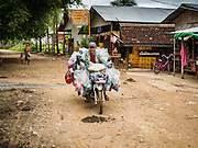 21 JUNE 2016 - DON KHONE, CHAMPASAK, LAOS: There are no markets on Don Khone so a couple of motorcycle owners have turned their bikes into rolling convenience stores. Don Khone Island, one of the larger islands in the 4,000 Islands chain on the Mekong River in southern Laos. The island has become a backpacker hot spot, there are lots of guest houses and small restaurants on the north end of the island.       PHOTO BY JACK KURTZ