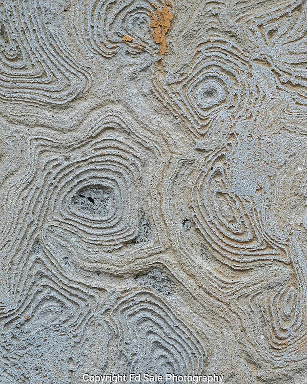 Swirls and lines created by adhesive adorn the side of a building forming unique shapes reminiscent of a maze with lines resembling rivers in a satellite photo