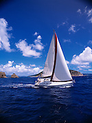 A sailboat cruises through the carribean waters off the British Virgin Islands