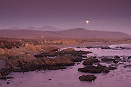 Evening moonrise over hills and rock coast at Piedras Blancas, near San Simeon, California
