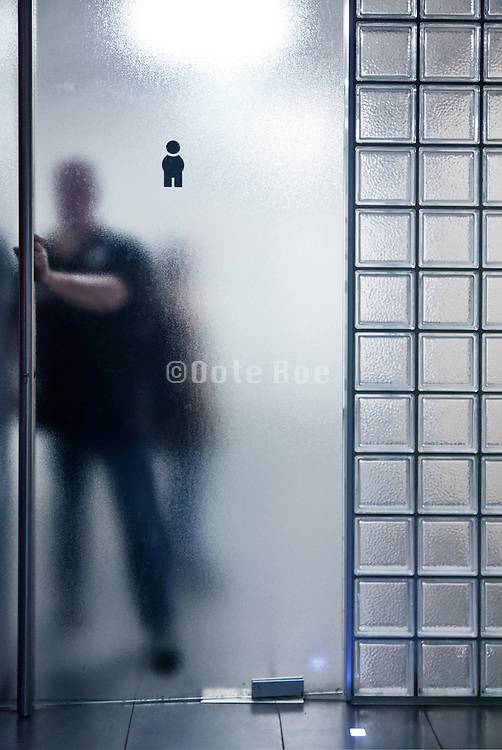 male toilette symbol with person entering the frosted glass door