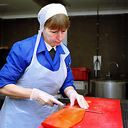 Isabel Cruden hand slicing smoked salmon at Andy Race Fish Merchants, Mallaig, Scotland, UK. Based in the port of Mallaig in the Highlands of Scotland, Andy Race Fish Merchants is renowned for producing the very best Scottish peat smoked salmon, Mallaig Kippers and a variety of high quality smoked fish and shellfish - all traditionally smoked with no dyes.