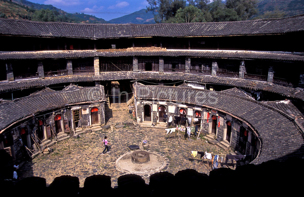 Shengwu Lou round earth dwelling in the village of Jiaolu, Fujian Province.  Interior circular courtyard and living spaces with central water well, shared by residents and chickens and hens alike. ar These are some of the most extraordinary multistory structures in China built exclusively out of earth and timber (they are known as tulou). From the outside they look and protect like fortresses, built principally by the ethnic minority group known as the Hakka. They where built principally in the 17th till the early 20th centuries. In all about 1000 remain standing today mostly centered around the mountainous regions of the provinces of Fujian, Jiangxi and Guandong. They where constructed in various shapes from circular, square, oblong,even rhomboid. Shengwu Lou, was built sometime in the Qing Dynasty ( 1644-1912) and still remains well preserved and lived in by a hand full of residents. The single - story inner ring and three -story outer ring are divided into 15 apartments that surround a courtyard  with a water well. Cooking and eating facilities are at ground level and all bedrooms and storage are spread over the upper floors.