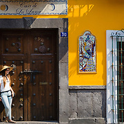 Woman posing in the doorway of a colourful house in Puebla, Mexico