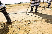 """05 JULY 2001 -- PHOENIX, AZ:  Members of the women chain gang in Maricopa County, Phoenix, AZ, clean up the county's """"Potter's Field"""" or cemetery for the indigent. Maricopa county sheriff Joe Arpaio claims to have the only women's chain gang in the United States. He has been criticized for the chain gang but claims to be an """"equal opportunity incarcerator."""" He has said that if puts men on a chain gang he will also put women on a chain gang. The women are prisoners in the county jail and volunteer for duty on the chain gang because it gets them out of the jail for six hours a day. The chain gang also buries the county's homeless and indigents. PHOTO BY JACK KURTZ"""