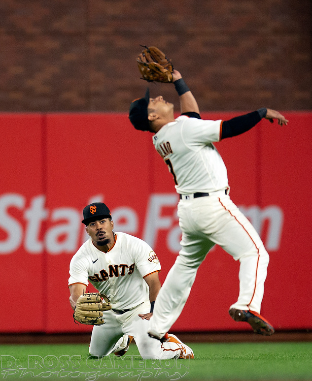 Sep 29, 2021; San Francisco, California, USA; San Francisco Giants second baseman Donovan Solano (7) nearly collides with right fielder LaMonte Wade Jr. (31) while pursuing a popup off the bat of Arizona Diamondbacks right fielder Henry Ramos during the sixth inning at Oracle Park. Mandatory Credit: D. Ross Cameron-USA TODAY Sports