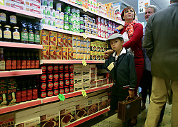 © Licensed to London News Pictures. 14/09/2012. Goodwood, UK A young boy dressed as an Evacuee with his mother. Tesco supermarket has recreated a sixties style branch of one of it's stores at The Goodwood Revival. Customers can browse items from the period and the staff are all wearing vintage uniform. People enjoy the atmosphere at the 2012 Goodwood Revival. The event recreates the glorious days of motor racing and participants are encouraged to dress in period dress. Photo credit : Stephen Simpson/LNP
