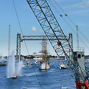 The U.S. Coast Guard Eagle sails into Portsmouth Harbor on August 2, 2013, to participate in Sail Portsmouth, hosted by the Piscataqua Maritime Commission. This view is framed by the crane at the Salt pile in the foreground, the just-finished Memorial Bridge II (note tiny workers standing on raised section), and the Portsmouth Naval Shipyard prison in the background.