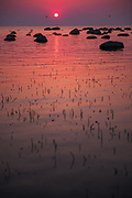 Sun slowly sets behind the sea while coloring the rocky seacoast in various shades and reds, near Bērzciems, Kurzeme seacoast, Latvia Ⓒ Davis Ulands | davisulands.com