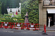Two models on a street shoot with the background of hanging hoarding media, of a Dior shop being refurbished in central London. Pausing during being filmed across the street, the two young people stand on the pavement, their scale and perspective looking incongruous to the barriers placed against the illustration that shows an incongruous fantasy garden with models placed around the landscape while construction work carries on in front and behind the screen. The Dior store occupies a prime location on one of London's most prestigious streets known for fashion and jewellery and work continues behind the screen, hidden to passers-by.