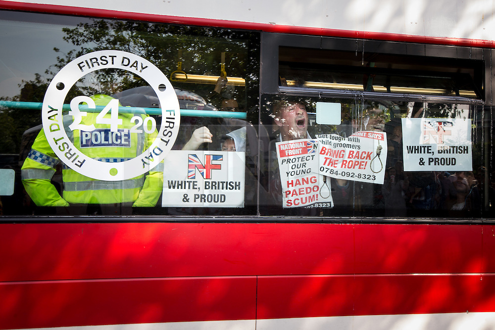 """© Licensed to London News Pictures . 22/08/2015 . Manchester , UK . Demonstrators are driven away on a coach . Far-right nationalist group , """" North West Infidels """" and Islamophobic , anti-Semitic and white supremacist supporters , hold a rally in Manchester City Centre . Photo credit : Joel Goodman/LNP"""
