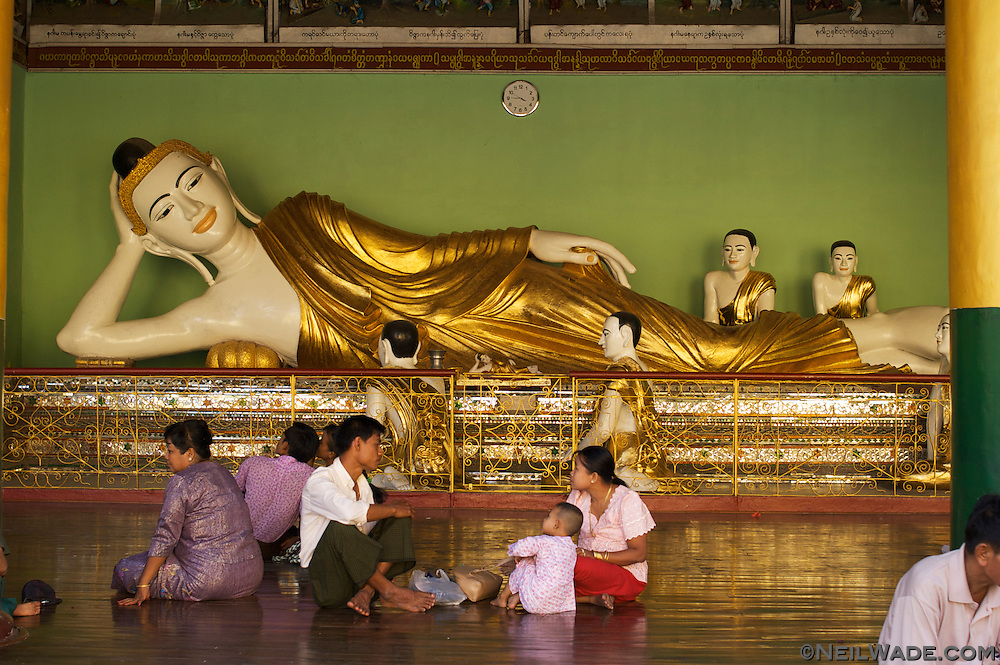 People relax by a reclining Buddha statue at Shwedagon Pagoda in Yangon, Myanmar.
