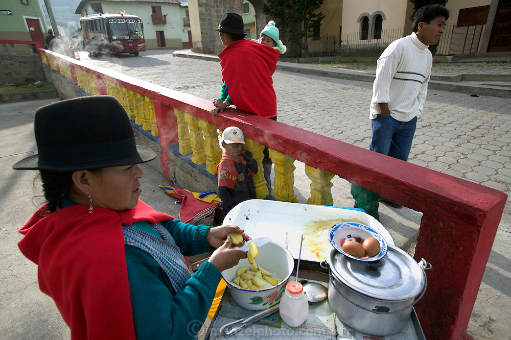 In the town plaza in Simiatug, Ecuador, a woman sells a large paper cone of fried potatoes to people waiting for busses or passing by for 25 cents US. (Supporting image from the project Hungry Planet: What the World Eats.)