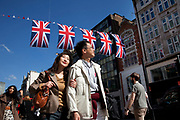 Shoppers and Union Jack flags in central London on Oxford Street, UK. This is the most famous street in the UK for shopping and mid range retail, and is consequently one of the busiest shopping streets in the country. As Britain prepares for the Queen's Diamond Jubilee and the London 2012 Olympics, the scenes of national pride are becomming common.
