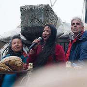 First Nation woman Kiera Dawn-Kolson speakes to the crowd from the polar bear flanket by fellow First Nation lady and John Sauven, director of Grenpeace. She lives in Canada and her land is endangered by Shell and other oil drilling companies. The giant polar bear puppet Aurora made by Greenpeace walked the streets of London in defence of the Arctic as part of a Greenpeace global day of action. The parade,part performance part protest, was to highlight the melting ice caps and the increasing and potentially devastating oil drilling in the arctic sea. Shell is one of the companies drilling and the march through London ended up outside Shell London HQ to draw attention to their oil business in the arctic. Aurora, the biggest polar bear in the world represents all endangered species in arctic.
