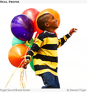 Advertising image of African American boy smiling and holding balloons. Billboard for Puget Sound Blood Center.