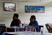 Two men watch television in a restaurant, Quincemil adjacent to the Interoceanic Highway