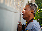 26 DECEMBER 2013 - BANGKOK, THAILAND: A neighborhood resident looks through a block wall while taking cover from police who were firing rubbet bullets. Thousands of anti-government protestors flooded into the area around the Thai Japan Stadium to try to prevent the drawing of ballot list numbers by the Election Commission, which determines the order in which candidates appear on the ballot of the Feb. 2 election. They were unable to break into the stadium and ballot list draw went as scheduled. The protestors then started throwing rocks and small explosives at police who responded with tear gas and rubber bullets. At least 20 people were hospitalized in the melee and one policeman was reportedly shot by anti-government protestors.      PHOTO BY JACK KURTZ
