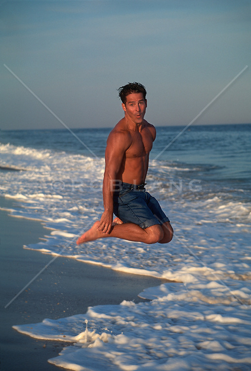 Cute good looking man jumping in mid air above ocean waves