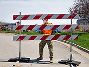 """26 APRIL 2020 - DES MOINES, IOWA: A soldier with the Iowa Army National Guard opens the gate of the COVID-19 drive through testing site in Des Moines. Iowa started mass testing Saturday, with a drive through testing site in a parking lot in downtown Des Moines. The testing this weekend is considered a """"soft opening"""" for the program and tests were reserved for medical professionals and first responders. Despite numerous outbreaks in meat packing plants throughout Iowa, members of the public have not been able to get tested. On Saturday, 25 April, there were 5,092 confirmed cases of COVID-19 (Coronavirus / SARS-CoV-2) in Iowa (an increase of 647 since Friday, April 24) and 112 deaths in Iowa caused by COVID-19.                PHOTO BY JACK KURTZ"""