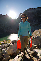 A young woman hauls water bags above Timberline Lake in Grand Teton National Park, Jackson Hole, Wyoming.
