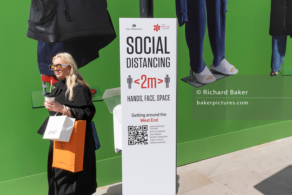 A woman walks past a Covid social distancing sign beneath the temporary construction hoarding for Balenciaga, a retail space which is opening soon on Bond Street, on 27th April 2021, in London, England. Balenciaga is a fashion house founded in 1917 by Spanish designer Cristóbal Balenciaga in San Sebastián, Spain.