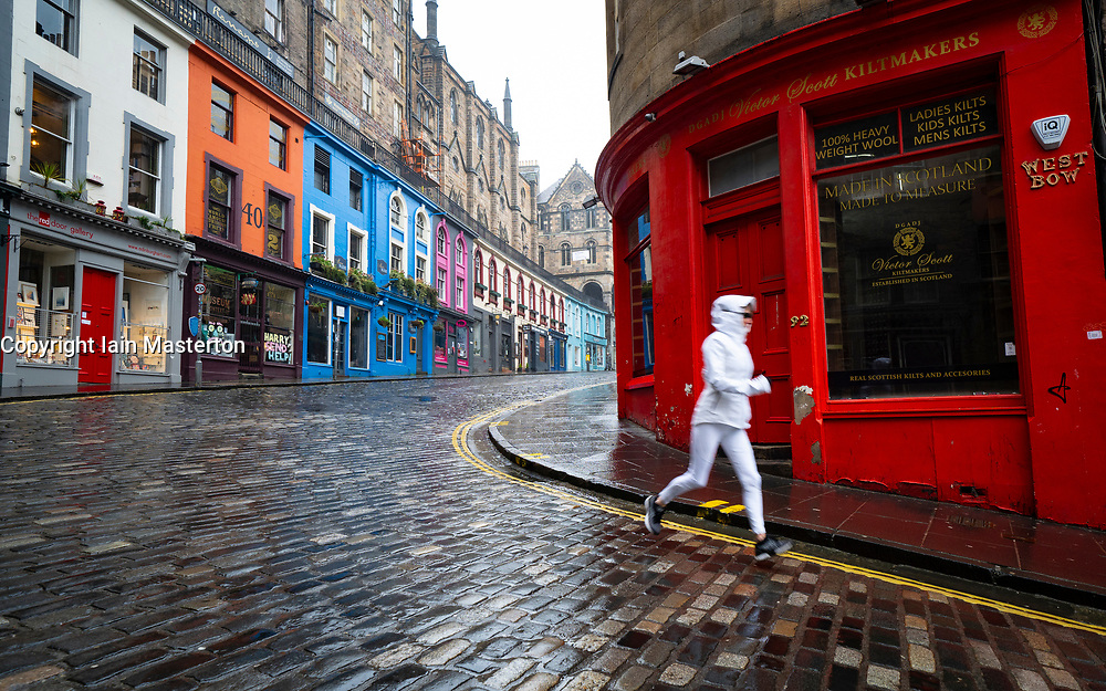 Edinburgh, Scotland, UK. 20 January 2020. Views of quiet streets in Edinburgh city centre on day after First minister Nicola Sturgeon announced national lockdown would be extended into February. Streets remain very quiet with no non essential shops open. Pic; lone jogger runs on an empty Victoria Street in the Old town.  Iain Masterton/Alamy Live News