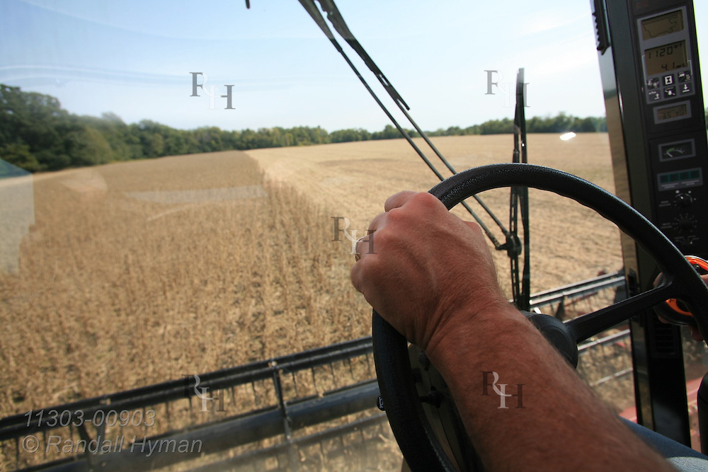 Farmer's hand rests on steering wheel as he drives combine and harvests soybean crop in September; Paris, Illinois.