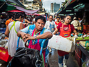 "12 JUNE 2015 - BANGKOK, THAILAND: A porter waits for customers in Khlong Toey Market in Bangkok. Khlong Toey (also called Khlong Toei) Market is one of the largest ""wet markets"" in Thailand. The market is located in the midst of one of Bangkok's largest slum areas and close to the city's original deep water port. Thousands of people live in the neighboring slum area. Thousands more shop in the sprawling market for fresh fruits and vegetables as well meat, fish and poultry.          PHOTO BY JACK KURTZ"