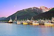Alaska, Seward, Fishing boats at dock on Resurrection Bay with a Moon setting.