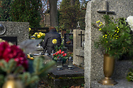 A woman remembers her deceased loved ones at Rakowicki Cemetery in Krakow, Poland 2019.