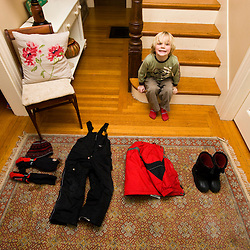 A young boy (age 5) prepares to go outside in the winter in Portsmouth, New Hampshire.