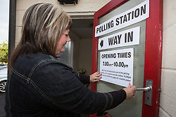 © Licensed to London News Pictures . 07/05/2015 . Doncaster , UK . A woman sticks a POLLING STATION sign outside the door of Sutton Village Hall polling station in Ed Miliband's constituency of Doncaster North. Photo credit : Joel Goodman/LNP