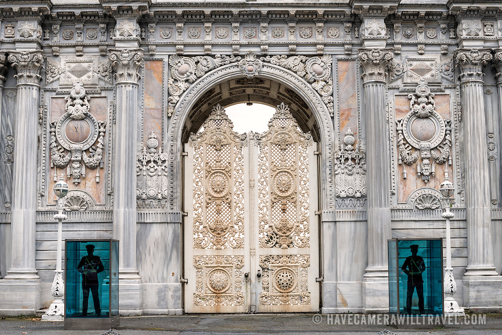A pair of guards stand on duty outside an ornately decorate gate at Dolmabahçe Palace. Dolmabahçe Palace, on the banks of the Bosphorus Strait, was the administrative center of the Ottoman Empire from 1856 to 1887 and 1909 to 1922. Built and decorated in the Ottoman Baroque style, it stretches along a section of the European coast of the Bosphorus Strait in central Istanbul.