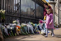 © Licensed to London News Pictures. 09/04/2021. London, UK. Nevaeh, 7, lays flowers outside Buckingham Palace with her mother, Tasha Pettman, following news of the death of Prince Philip. The Duke of Edinburgh Prince Philip, Queen Elizabeth II's husband, has died aged 99 Buckingham Palace has announced. Photo credit: Rob Pinney/LNP