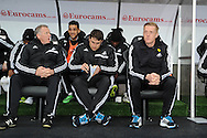 Swansea city's manager Garry Monk (r) with his coaching staff sits in dugout ahead of k/o. Barclays Premier league, Swansea city v Crystal Palace match at the Liberty Stadium in Swansea, South Wales on Sunday 2nd March 2014.<br /> pic by Andrew Orchard, Andrew Orchard sports photography.
